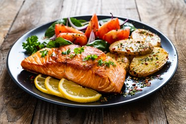 air fryer salmon steak, fried potatoes and vegetables on wooden background
