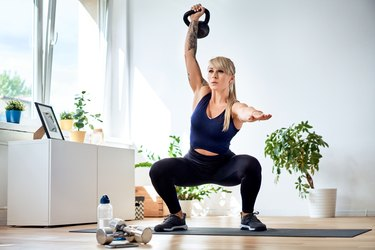 Athletic woman doing kettlebell overhead squats in her living room at home