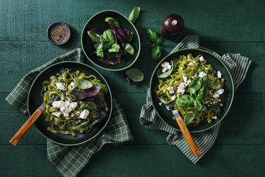 top view of two bowls of green vegetable pasta and a smaller bowl of green salad on a green tablecloth