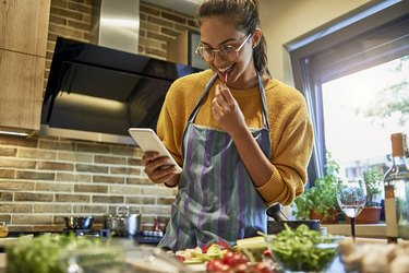 beautiful young woman using her smartphone while cooking