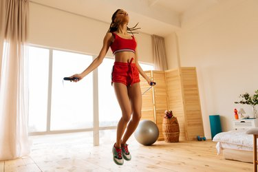 woman wearing red shorts and sneakers jumping rope at home