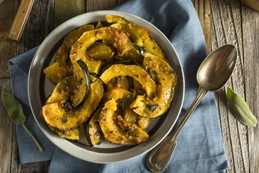 Homemade sliced and baked potassium-rich acorn squash on a plate on a wooden table with spoon on the side