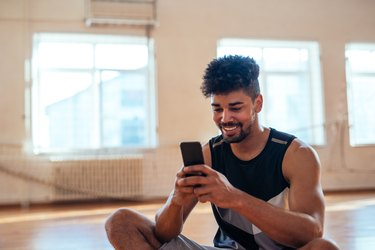 Man texting on his phone during a workout
