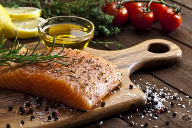Raw salmon steak on wooden board with oil and veggies
