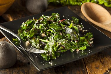 Sauteed magnesium- and potassium-rich Swiss chard on a black plate with a fork