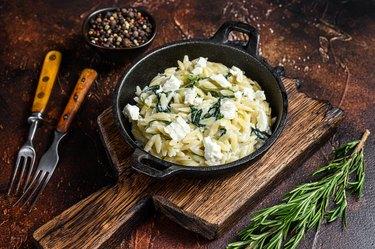 gluten-free Orzo primavera with green veggies spinach. Dark wooden background