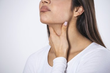 Young beautiful woman suffering from pain in throat, touching inflamed zone on her neck, cropped, empty space, sore throat