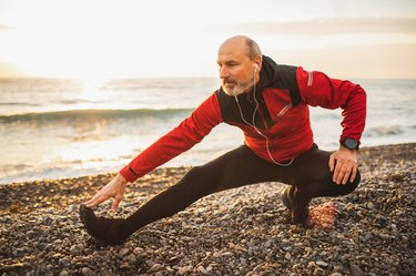 Senior adult male runner stretching legs and warming up outdoors before running training