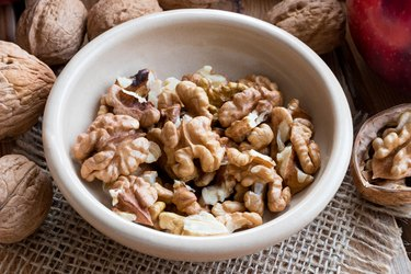 Shelled walnuts in a bowl, with whole walnuts and an apple