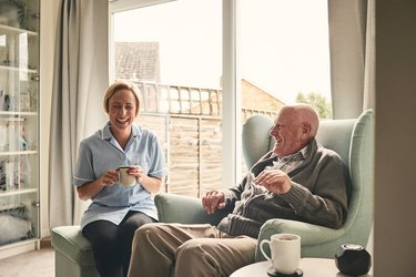 Senior man with COPD and female carer enjoying coffee at home