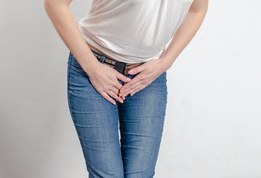 young woman pressed her hands to her lower abdomen.