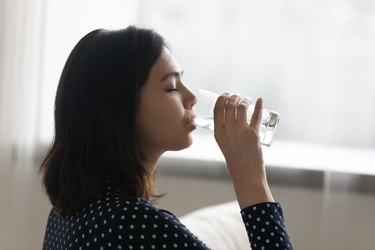 Young multiracial asian korean woman drinking cool distilled water.