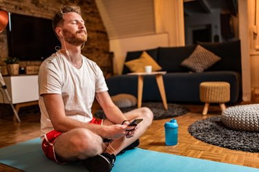 Young man relaxing at home with guided meditation.