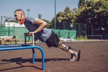 Man doing incline triceps push-ups outdoors