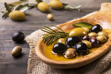 Healthy fat-rich olives with rosemary in the foreground