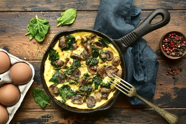 Omelette with mushrooms and spinach in a cast iron pan
