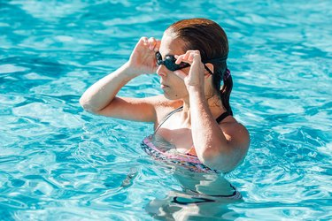 woman in swimming pool putting on swimming goggles, getting started with swimming for beginners