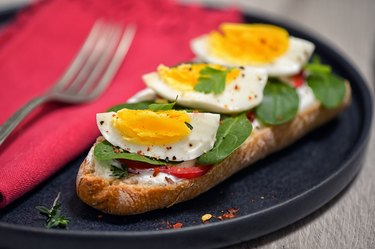 Meal with soft boiled eggs, toast, yogurt and spinach