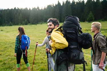 group of happy young friends hiking together with backpacking backpacks