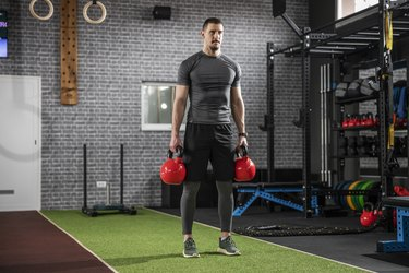 caucasian man doing the kettlebell farmer's walk exercise with two kettlebells in the gym
