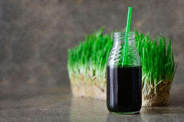 A bottle of liquid chlorophyll with a straw in front of a slab of wheatgrass