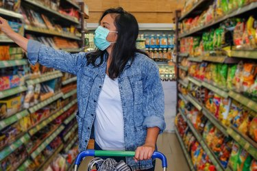 A woman wearing a face mask while shopping in an aisle of the grocery store