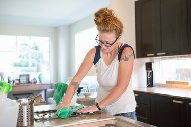 Young woman cleaning kitchen with green cleaning products to improve indoor air quality