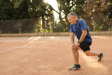 Concentrated senior man warming up and exercising on tennis court. Active lifestyle of old people