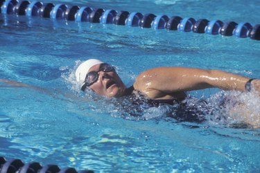 person wearing cap and goggles swimming laps in a pool