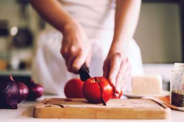 close view of a person slicing fresh, red tomatoes on a wooden cutting board