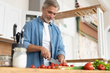 Grey-haired Mature handsome man preparing delicious and healthy food in the home kitchen.