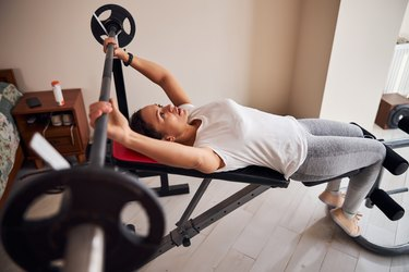 woman doing a barbell bench press in her home
