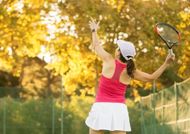 woman wearing white cap and skirt and red tank top serving a tennis ball outside