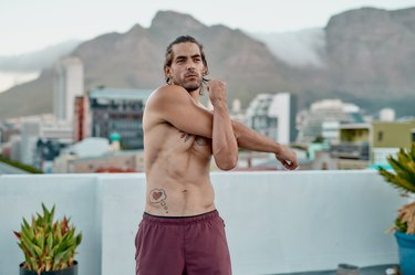 young muscular man doing dynamic arm stretches on a roof with the mountains in the background