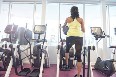 Rear view of mature woman at gym on step machine