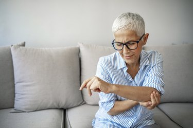 older caucasian woman sitting on the couch with elbow pain, needing to learn how to wrap a tennis elbow