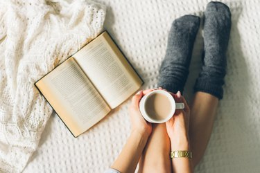 woman laying in bed and read book with cup if coffee