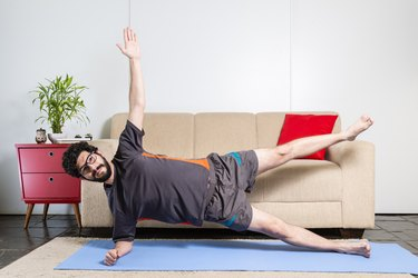 Beautiful caucasian bearded man in black clothes on blue yogamat doing side plank pose variation