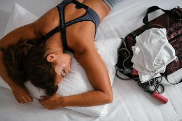 woman in workout clothes lying down on bed