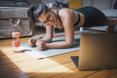 woman wearing glasses doing Pilates workout video at home with laptop and water bottle