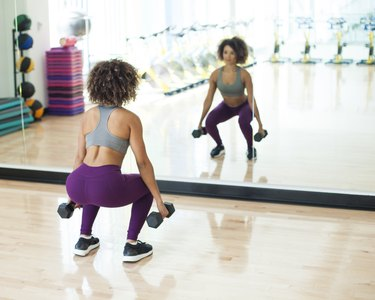 Woman doing a dumbbell squat to strengthen her glutes at the gym