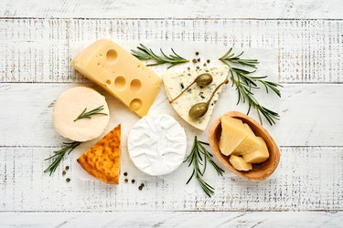 assortment of cheeses with camembert, blue cheese, parmesan, and brie on white wooden background