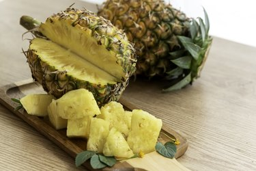 Fresh sliced pineapple on wooden tray on table