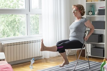 senior woman doing mobility exercises on a chair at home
