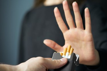 A person's hand refusing cigarettes, as a natural remedy for upset stomach