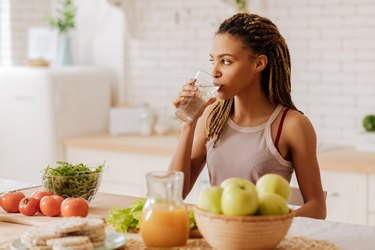 A woman in her kitchen at home drinking water to relieve constipation