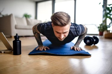 Front view portrait of man with tablet doing proper push-up form indoors at home.