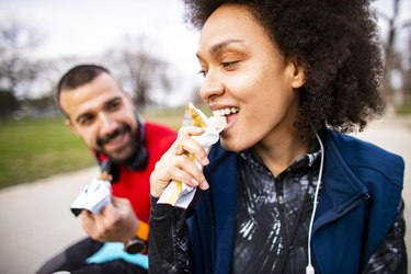 woman eating a healthy store bought snack outside with man on park bench