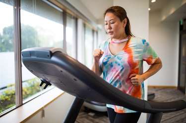 A woman running on a treadmill at a gym