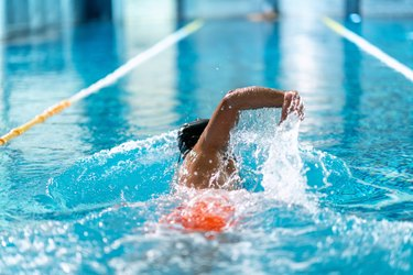 swimmer doing freestyle low-impact swimming workout in indoor pool